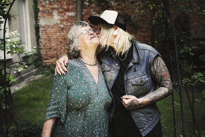Daughter kissing mother while standing in back yard - FSIF01882