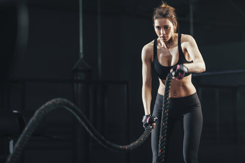 Young woman exercising with rope at gym - FSIF01942