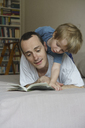 Father and son reading book while lying on bed at home - FSIF01954