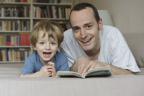 Portrait of smiling father and son lying on bed with book at home - FSIF01957