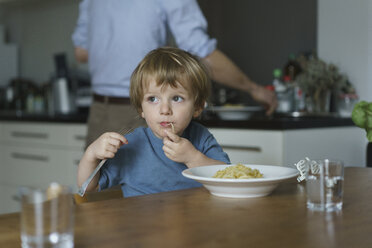 Boy eating noodles while father working in kitchen at home - FSIF01960