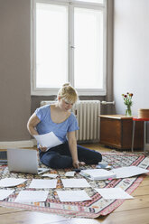 Woman doing paperwork while sitting on carpet at home - FSIF01975