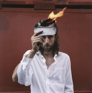 A man with a white shirt holding a piece of paper on fire - FSIF01984