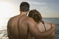 Couple embracing on beach at sunset - FSIF02086
