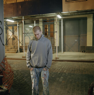 Young man standing in street at night - FSIF02092