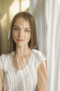 Portrait of smiling woman standing by curtains at home on sunny day - FSIF02173