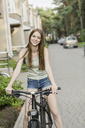 Smiling woman cycling on cobbled street against buildings in city - FSIF02176