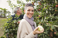Portrait of happy woman eating apple in orchard - FSIF02191