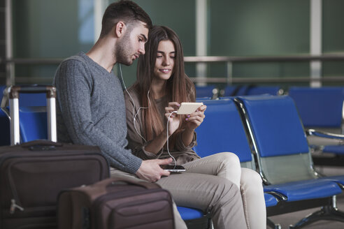 Young couple listening music through smart phone while waiting in airport - FSIF02215