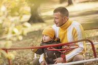 Thoughtful man sitting with baby boy on carousel at park during autumn - FSIF02266