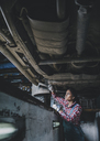 Female mechanic working underneath car at workshop - FSIF02269