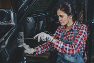 Female mechanic repairing car at workshop - FSIF02275