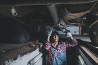 Female mechanic holding flashlight while working underneath car at workshop - FSIF02278