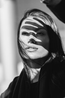 Shadow of hand on thoughtful woman's face during sunny day - FSIF02281