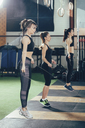 Side view of female athletes exercising with jump ropes at gym - FSIF02302