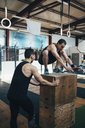 Male athlete assisting friend in doing box jumping at gym - FSIF02305