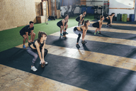 High angle view of determined athletes exercising with kettlebells at health club - FSIF02311