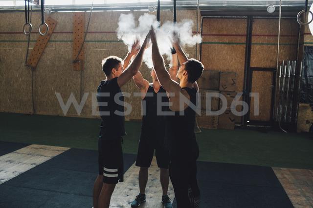 Determined sportsmen dusting sports chalk together at gym - FSIF02314 - fStop/Westend61