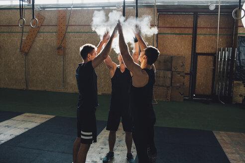 Determined sportsmen dusting sports chalk together at gym - FSIF02314
