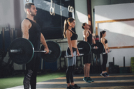 Side view of male and female athletes lifting barbells at health club - FSIF02317