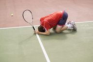 A tennis player crouching on the floor in defeat - FSIF02416