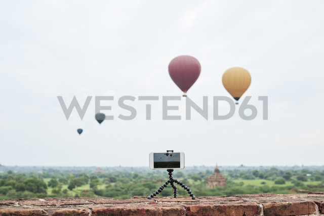 Myanmar, smartphone taking a time lapse of many hot air balloons flying over Bagan - IGGF00432