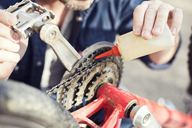 Man oiling bicycle chain, close-up - MAEF12531