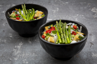 Bowl of vegan Pad Thai with mini green asparagus and tofu, chili, spring onion, peanut and coriander - LVF06726