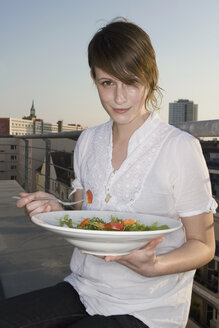 A young woman sitting on a rooftop terrace holding a plate of salad - FSIF02525