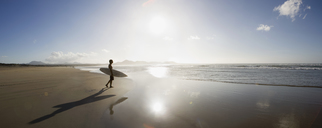 A young man standing on a beach and carrying a surfboard - FSIF02564