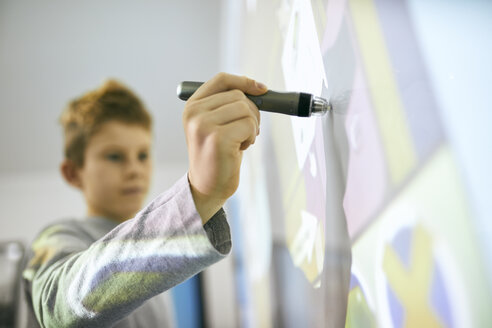 Student in class using digitized pen at interactive whiteboard - ZEDF01195