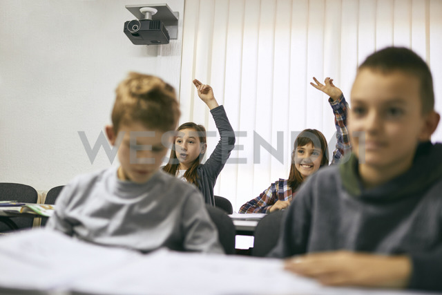 Students in class with two girls raising their hands - ZEDF01204
