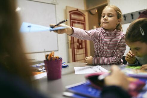 Schoolgirlhanding over sheet of paper to classmate in class - ZEDF01216