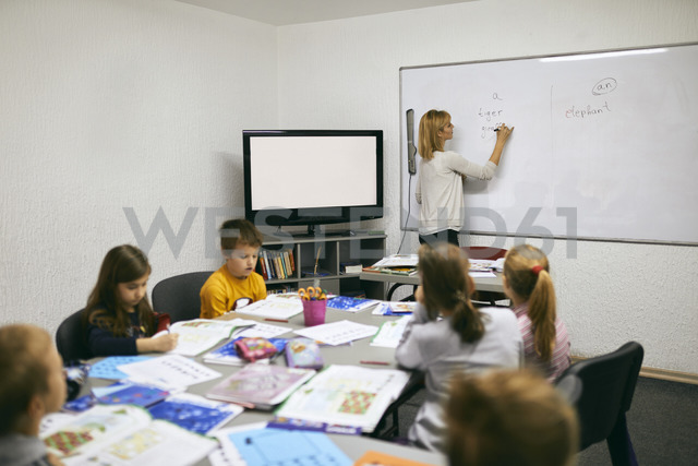 Teacher writing on whiteboard in class - ZEDF01219 - Zeljko Dangubic/Westend61
