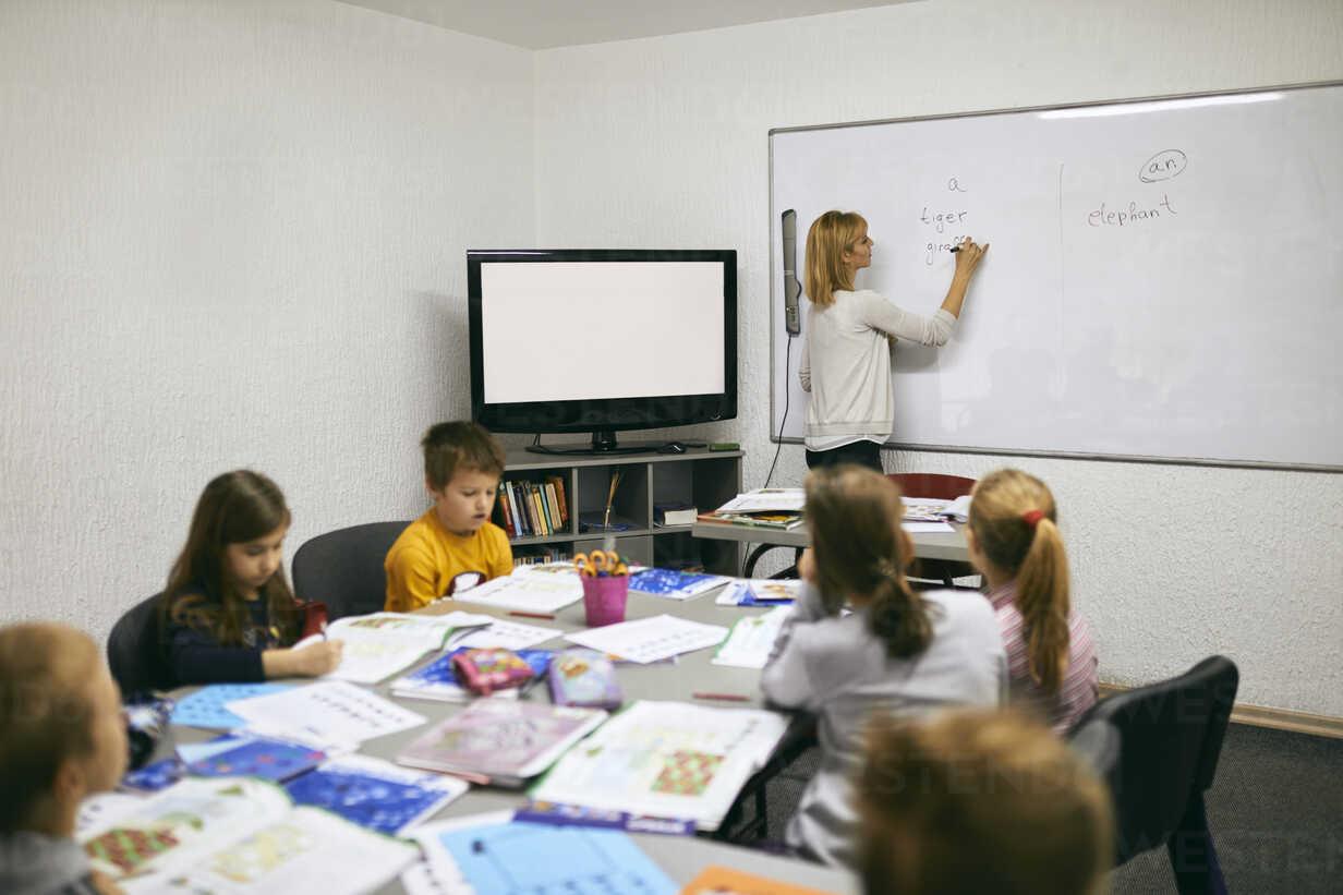 Teacher writing on whiteboard in class - ZEDF01219 - Zeljko Dangubic/Westend61