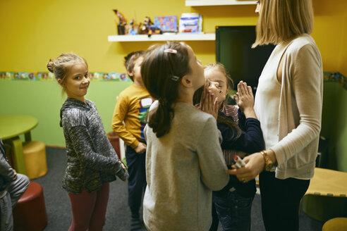 Teacher standing with students in class - ZEDF01222