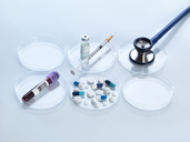 Stethoscope, vaccine, blood sample and variety of medicine in petri dish - ABRF00108