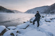 Russia, Amur Oblast, man standing at riverside of Bureya in winter - VPIF00316