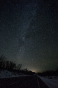 Russia, Amur Oblast, empty country road under starry sky in winter - VPIF00322