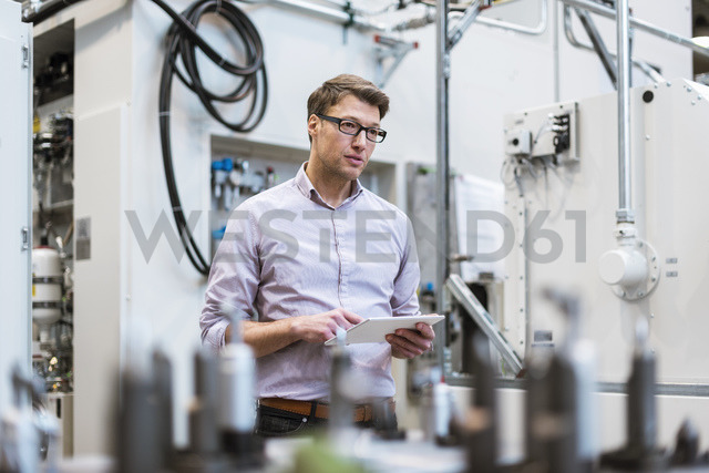 Businessman in factory holding tablet - DIGF03406