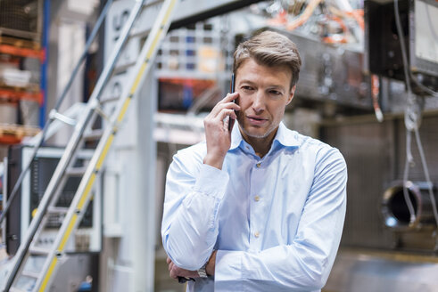 Businessman on cell phone in factory - DIGF03409