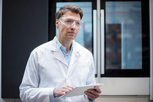 Portrait of man wearing lab coat and safety goggles holding tablet at machine - DIGF03412