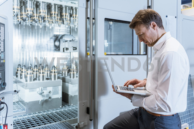 Businessman at machine in factory looking at laptop - DIGF03418