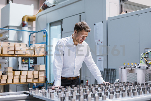 Businessman in factory looking at machine - DIGF03421