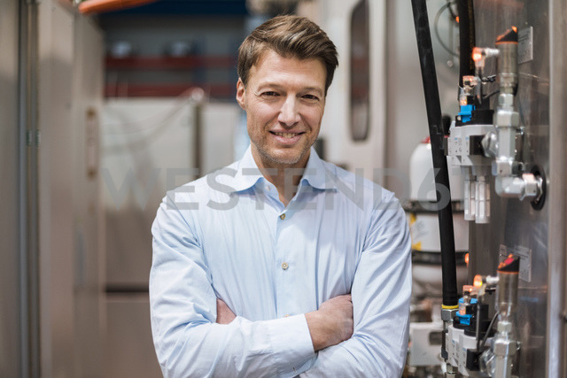 Portrait of smiling businessman at machine in factory - DIGF03424