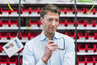 Portrait of confident businessman at shelf in factory storeroom - DIGF03427