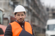 Portrait of content man wearing safety vest and helmet at construction site - SGF02188