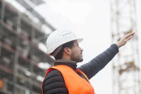 Man with wearing safety vest and hard hat at construction site - SGF02191