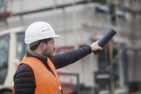Man wearing safety vest and helmet at construction site - SGF02194