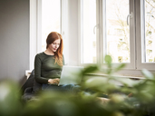 Redheaded woman sitting beside  window using laptop - FMKF04858